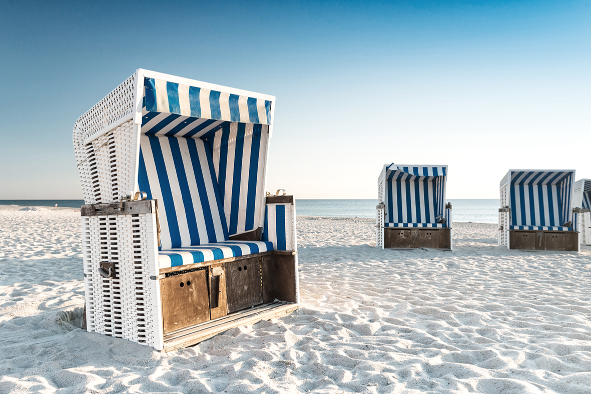 Beach - chairs on the island Sylt on sunset. Germany.