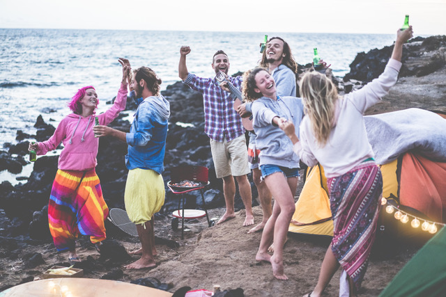 Happy friends dancing and making barbecue beach party – Adult surfer people having fun together drinking beer and camping next ocean – Focus on center man face – Fun, vacation and friendship concept